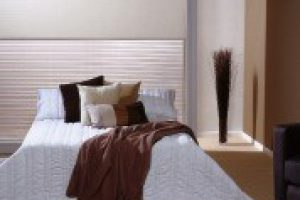 dual rollerblinds above bed in bedroom
