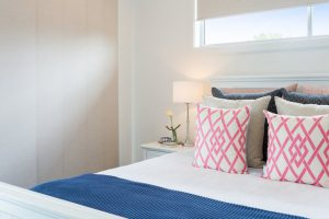 rollerblinds across small window above bed
